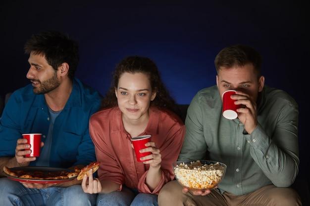 Gruppe von freunden, die filme zu hause schauen, während sie snacks und popcorn essen, die auf großem sofa im dunklen raum sitzen