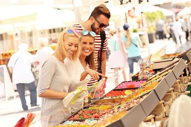 Gruppe von freunden, die geleebonbons auf dem markt kaufen