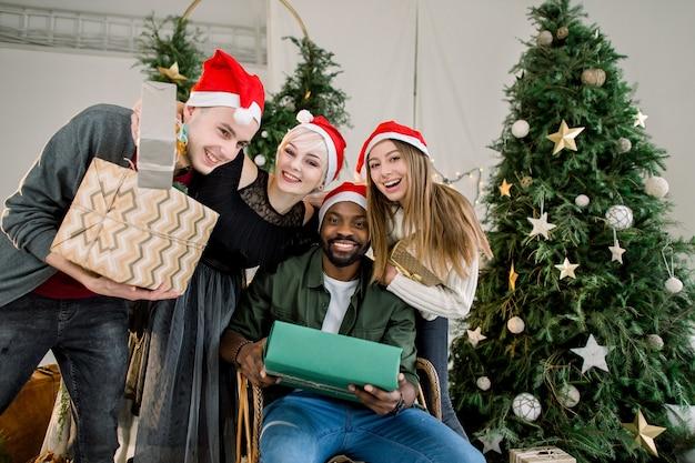 Gruppe von freunden, die geschenkboxen halten und weihnachten im dekorierten haus feiern