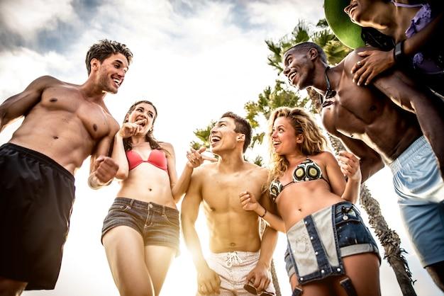 Gruppe von freunden, die große party und spiele am strand machen
