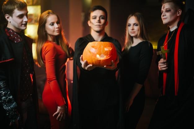 Gruppe von freunden, die halloween-typ mit fledermauskostüm feiern, hält kürbis