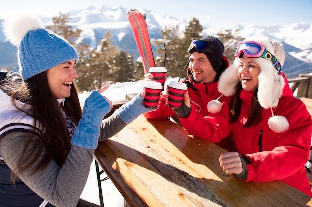 Gruppe von freunden, die heißen glühwein im cafe im skigebiet genießen.