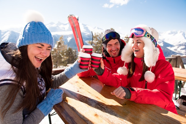 Gruppe von freunden, die heißen tee oder kaffee im cafe am skigebiet genießen