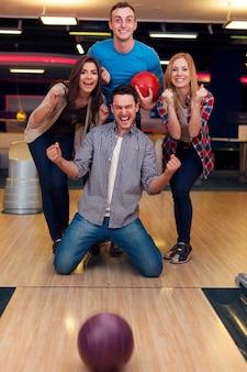 Gruppe von freunden, die im bowling spielen