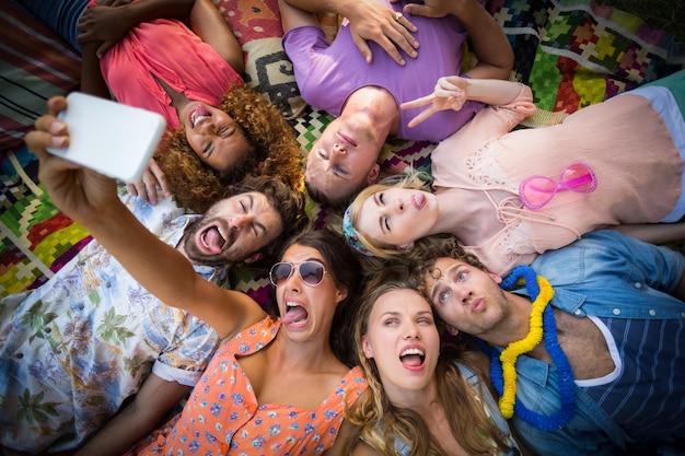 Gruppe von freunden, die im kreis liegen und ein selfie machen