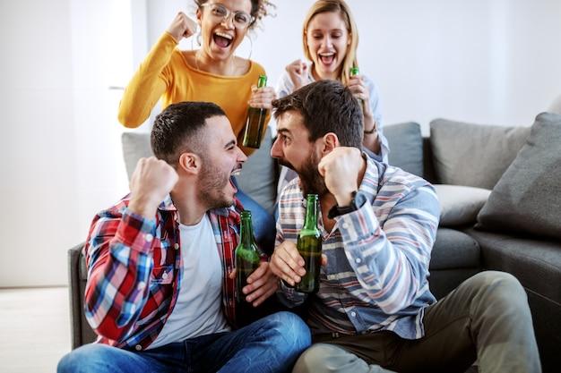 Gruppe von freunden, die im wohnzimmer sitzen und für ihre lieblingsfußballmannschaft jubeln. sie alle halten bierflaschen in der hand.