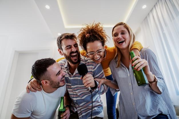 Gruppe von freunden, die karaoke-party zu hause haben. mann, der mikrofon hält, während andere bier halten.