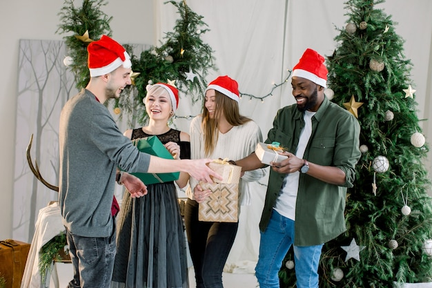 Gruppe von freunden, die lachen und weihnachtsgeschenke im schönen gemütlichen studio teilen