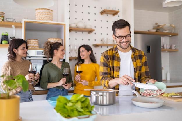 Gruppe von freunden, die mahlzeit in der küche vorbereiten