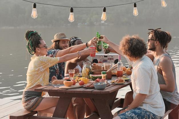 Gruppe von freunden, die mit bier rösten, während sie während des mittagessens auf einem pier am tisch sitzen