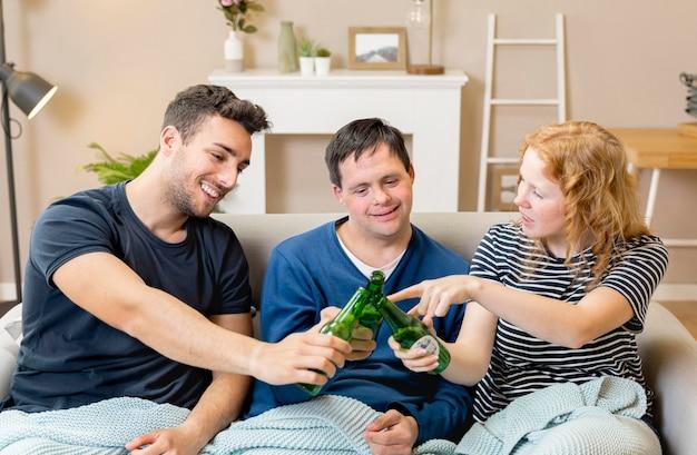 Gruppe von freunden, die mit bier zu hause jubeln