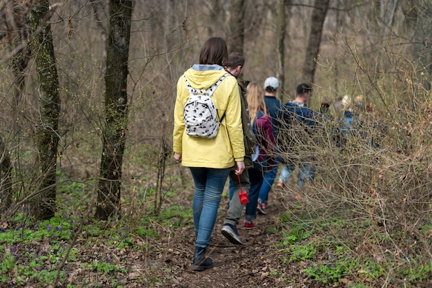 Gruppe von freunden, die mit rucksäcken im frühlingswald von hinten gehen. backpacker, die im wald wandern. abenteuer, reisen, tourismus, aktive erholung, wanderung und menschenfreundschaftskonzept.