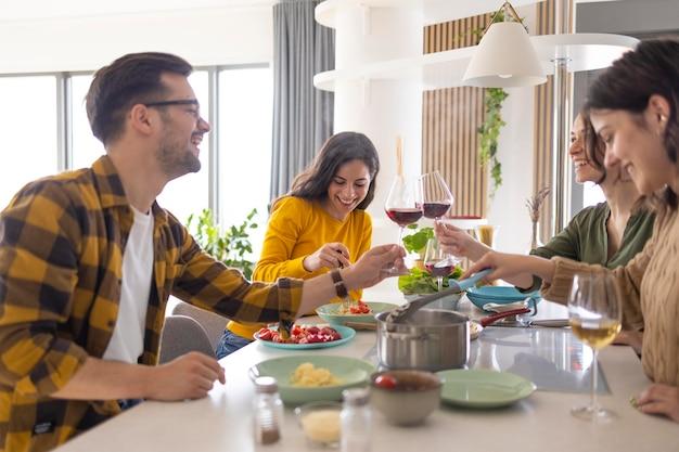 Gruppe von freunden, die mit wein in der küche rösten