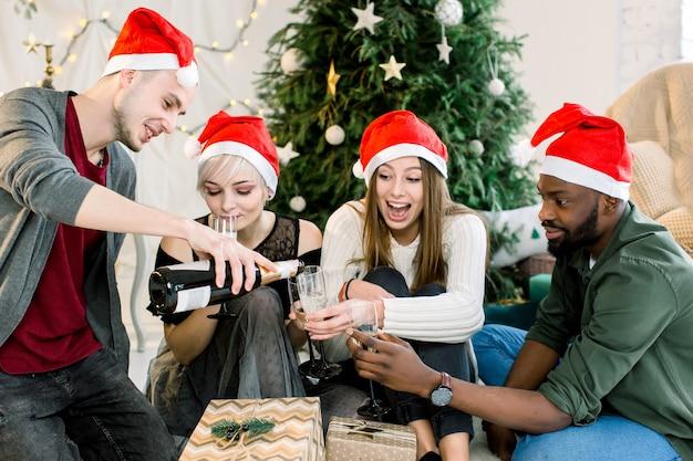 Gruppe von freunden, die neben weihnachtsbaum sitzen und chapmagne trinken