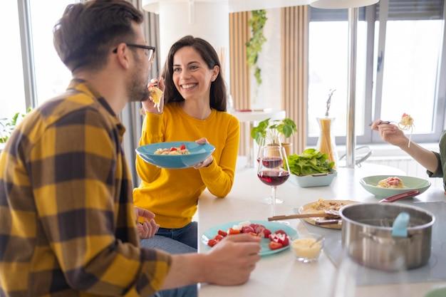 Gruppe von freunden, die nudeln zusammen in der küche essen