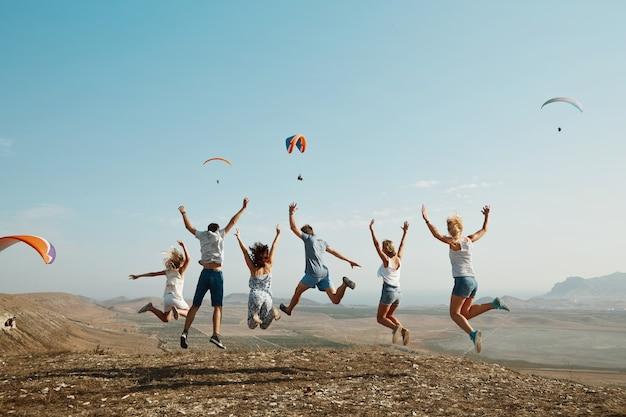 Gruppe von freunden, die oben auf hügel springen