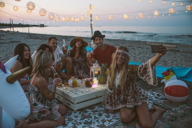 Gruppe von freunden, die party am strand zur sonnenuntergangszeit machen