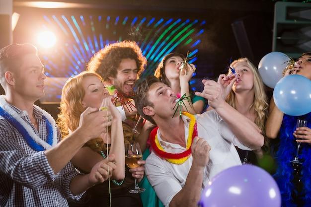 Gruppe von freunden, die partyhorn in der bar blasen