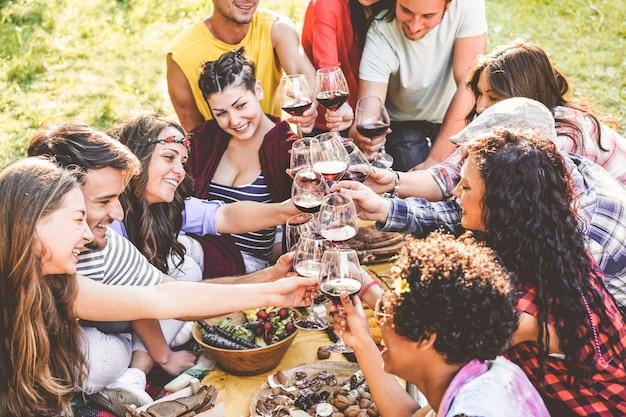 Gruppe von freunden, die picknick genießen, während rotwein trinken und snacks vorspeise im freien essen