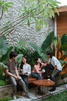 Gruppe von freunden, die sich unterhalten und einen kaffee genießen, während sie auf tisch und holzbank im hausgarten sitzen