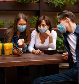 Gruppe von freunden, die smartphone betrachten, während sie etwas saft haben