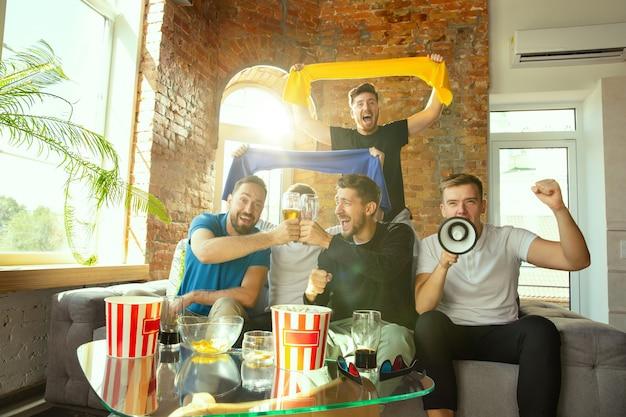 Gruppe von freunden, die spiel im fernsehen zu hause ansehen. sportfans verbringen zeit und haben spaß miteinander