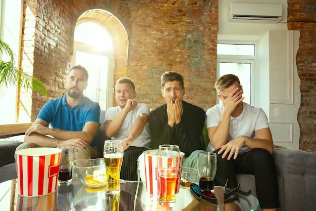 Gruppe von freunden, die spiel im fernsehen zu hause ansehen. sportfans verbringen zeit und haben spaß miteinander Kostenlose Fotos