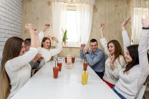 Gruppe von freunden, die turmspiel im café spielen