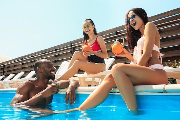 Gruppe von freunden, die während der sommerferien in einem schwimmbad spielen und sich entspannen