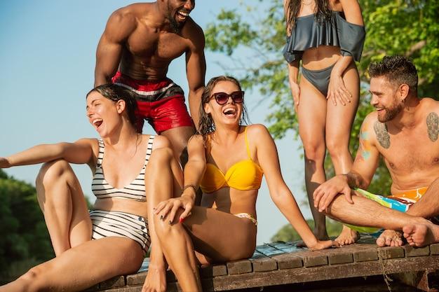 Gruppe von freunden, die wasser spritzen und auf pier am fluss lachen