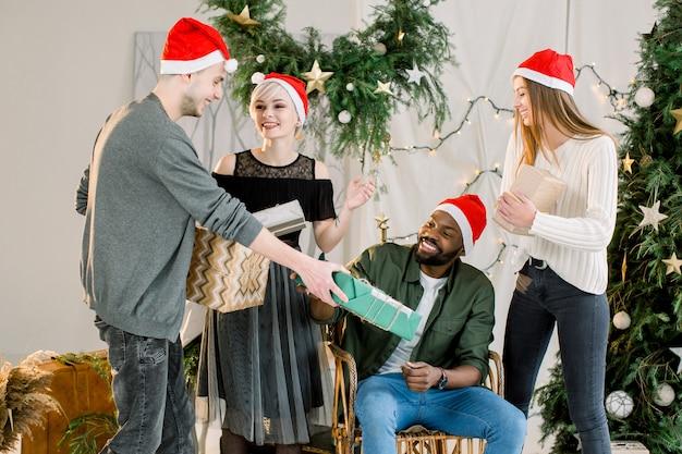 Gruppe von freunden, die weihnachten zu hause feiern und weihnachtsgeschenke austauschen