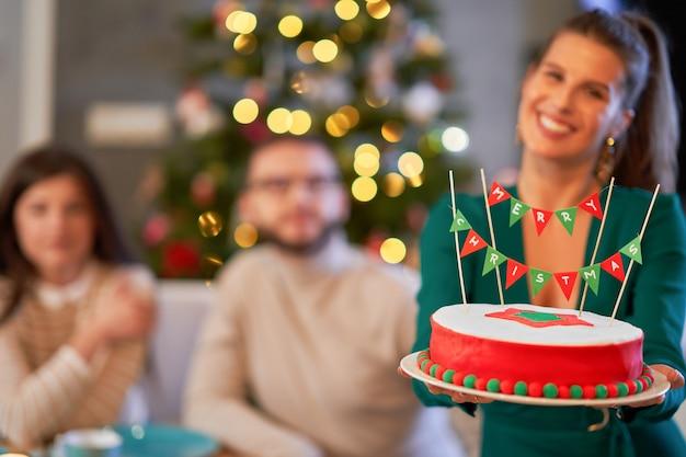 Gruppe von freunden, die weihnachten zu hause feiern und weihnachtskuchen genießen