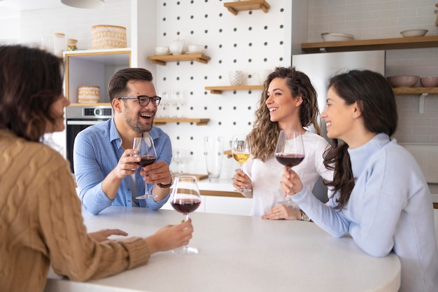 Gruppe von freunden, die wein in der küche trinken