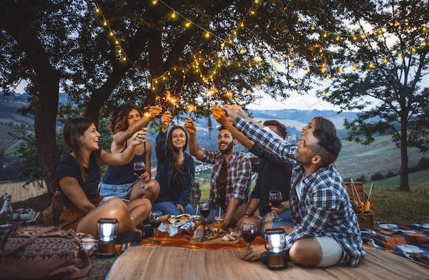 Gruppe von freunden, die zeit damit verbringen, ein picknick und einen grill zu machen