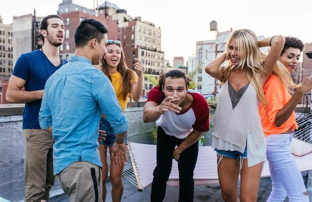 Gruppe von freunden, die zeit zusammen auf einem dach in new york city verbringen, lifestyle-konzept mit glücklichen menschen