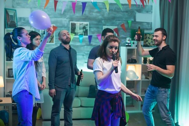 Gruppe von freunden, die zu hause karaoke spielen. menschen unterhaltung.