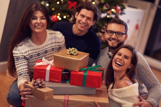 Gruppe von freunden, die zu hause weihnachtsgeschenke austauschen
