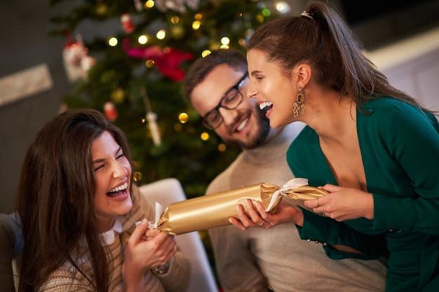 Gruppe von freunden, die zu hause weihnachtskekse ziehen