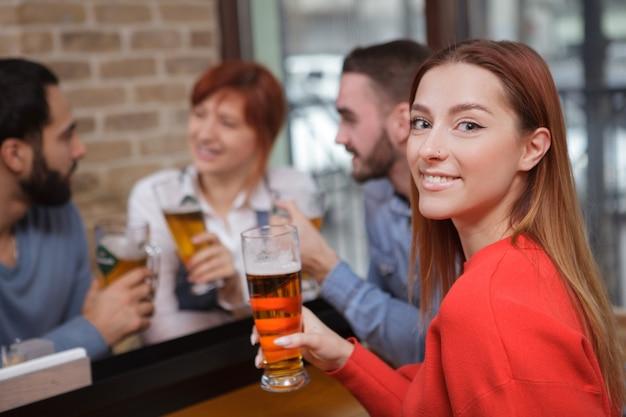 Gruppe von freunden, die zusammen bier in der kneipe trinken