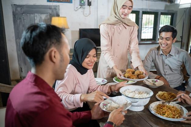 Gruppe von freunden, die zusammen zu mittag essen, während sie sich mit freunden treffen