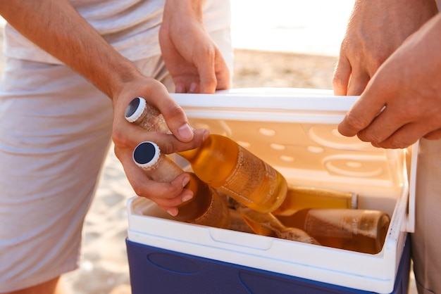 Gruppe von freunden draußen am strand, die kisten mit bier halten