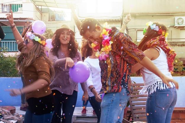Gruppe von freunden genießen auf dachspitze party und werfen konfetti