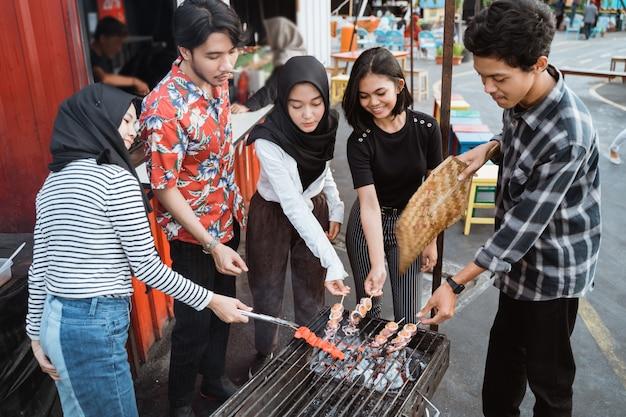 Gruppe von freunden grillen essen mit einem spieß