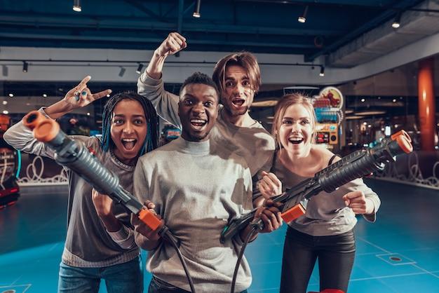 Gruppe von freunden in der spielhalle. afroamerikanerkerl mit gewehren.