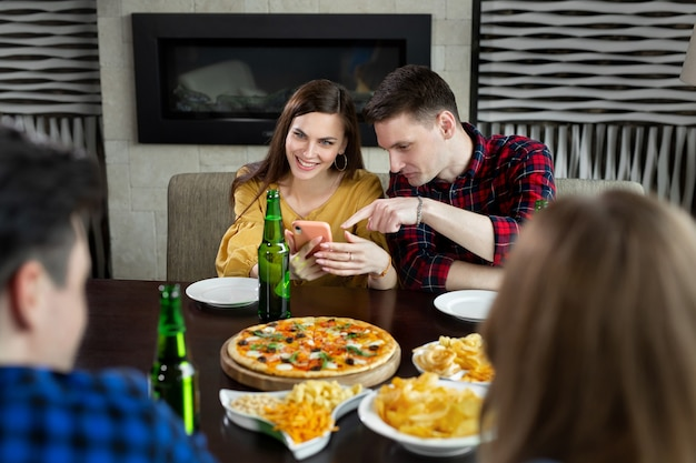 Gruppe von freunden in einem café mit pizza und bier, die spaß haben