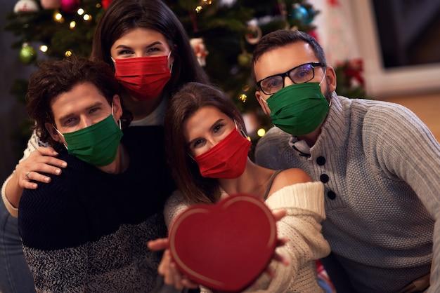 Gruppe von freunden in masken, die zu hause weihnachtsgeschenke austauschen