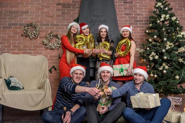 Gruppe von freunden mit champagner und luftballons auf der neujahrsparty