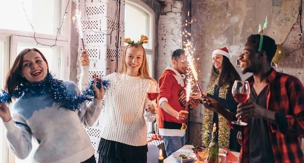 Gruppe von freunden mit feuerwerk auf einer party. junge freunde, die getränke trinken, um silvester zu feiern.