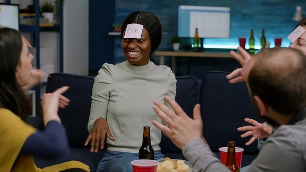 Gruppe von freunden mit haftnotizen, die raten, wer während der heimparty bier trinkt. multiethnische menschen, die spaß haben, zusammen lachen, während sie spät in der nacht auf dem sofa im wohnzimmer sitzen