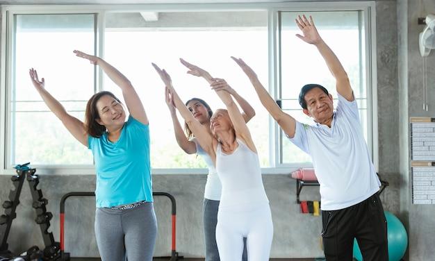 Gruppe von freunden senior dehnübungen im yoga-fitnessstudio mit trainer. älterer gesunder lebensstil.